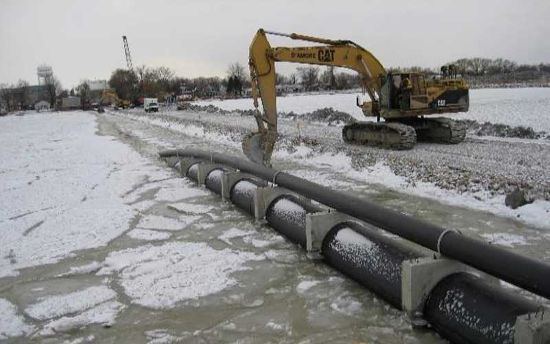 yellow construction crane beside long pipes in frozen water