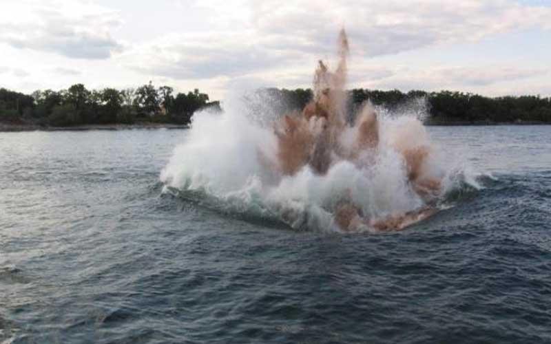 blast in body of water near shoreline of trees