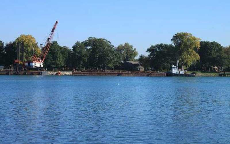 body of water in daytime near shoreline with trees and construction machinery
