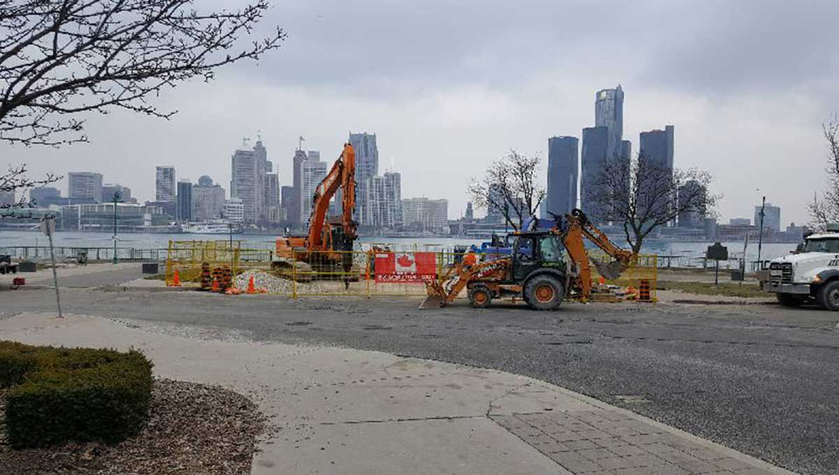 heavy machinery near waterfront in daytime with large buildings in the horizon