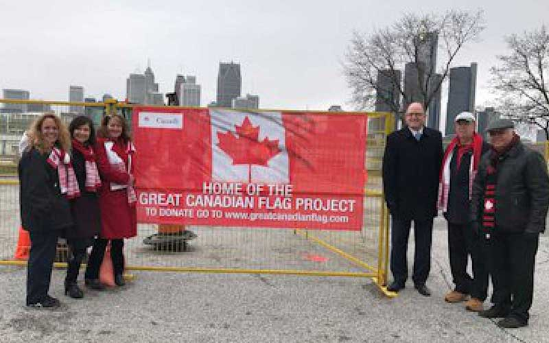 three people stand to the left of a canadian flag banner and three people stand to the right outdoors with buildings in the background