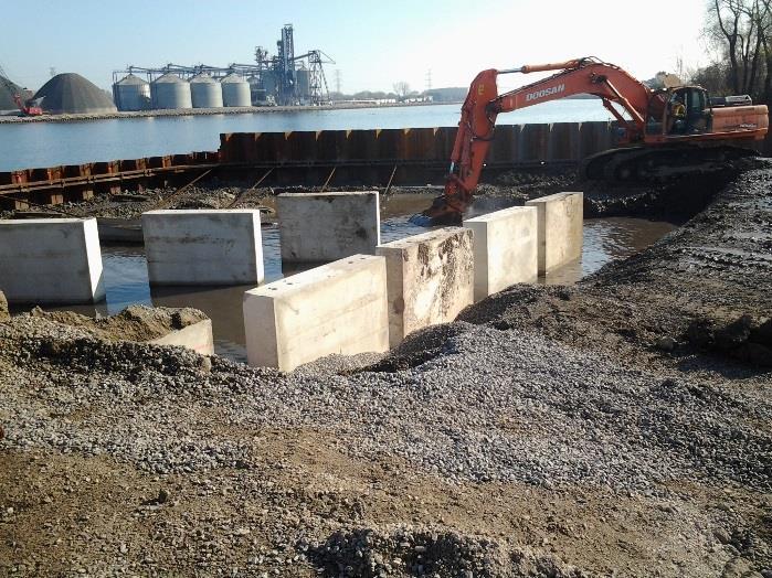 construction crane operating near large concrete blocks