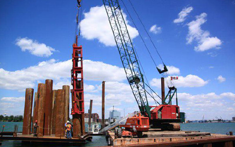 construction crane on platform close to body of water in daytime