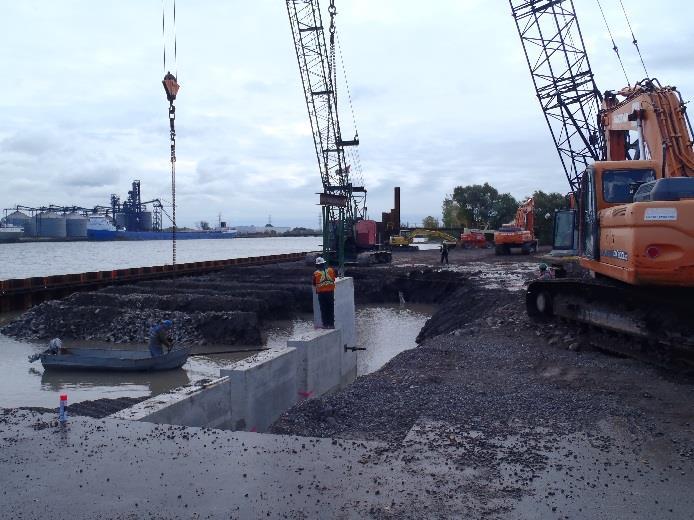 orange crane operating alongside construction workers near water